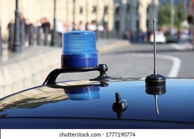 Blue flashing light and communication antennas on a government car on a city street. Concept of authorities, benefits and privileges of officials