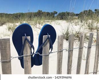 Blue flip flops on a beach fence.