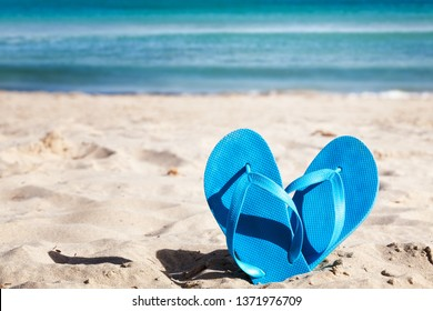 Blue flip flops on sand beach. Summer vacation concept
