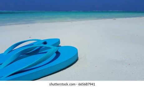 Blue flip flops on white sand beach with blue sea background