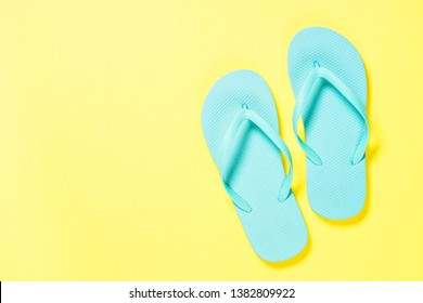 Blue flip flops on yelow. Top view.