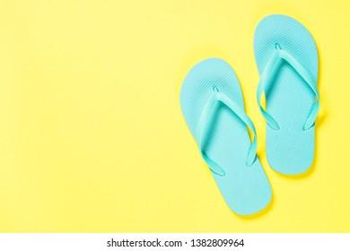 Blue flip flops on yelow. Top view.