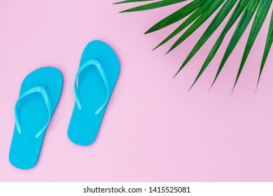 Blue flip flops shoes on pink background, top view, copy space. Toe sandals, flat lay, text place. Summer background with flipflop shoes and palm leaves