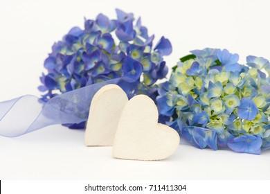 blue flower and wooden heart lying on white