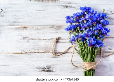 Blue flowers of cornflowers, rustic bouquet picked in summer located on wooden background