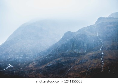 Blue foggy day in Scotland with a mountain in the background