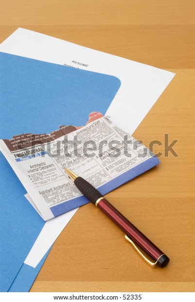 Blue folder with resume on desk, newspaper clipping and pen.