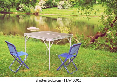 Blue folding camping chairs with a metal table on the green grass by the river in the evening forest