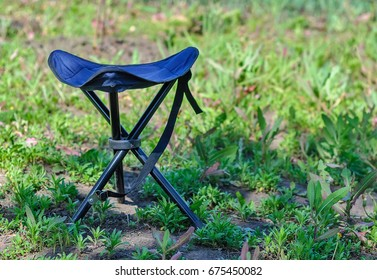 A blue folding high chair for camping on a summer green glade