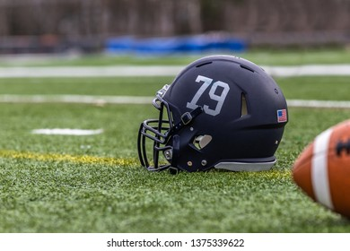 A blue football helmet is laying on the green field
