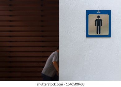 Blue frame of male symbol stick by screw nail head on rough white cement wall. Man customer wear gray t-shirt walking in men toilet with blurred dark brown plank wood s and sun lighting background.