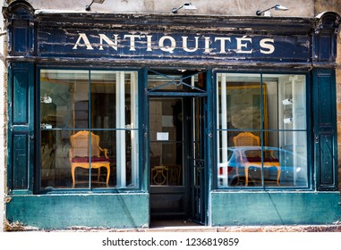 Blue French antique shop front with flaking paint in Beaune, Burgundy, France on 17 June 2013