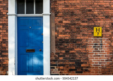 Blue Front Door with White Frame and Yellow Sign on Red Brick Wall in England