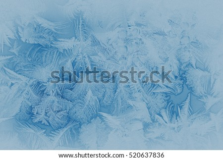 Blue frost pattern on a window glass in the winter (as an abstract winter background in subdued colors), retro style