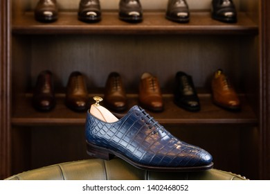 Blue full grain leather shoe in front of wooden display in men shoes boutique store.