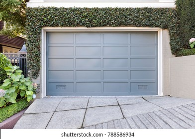 Blue garage door surrounded by ivy