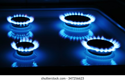 Blue gas stove in the dark with four rings of flame