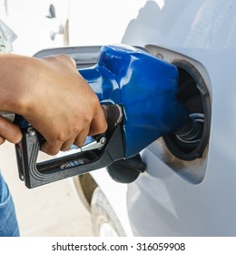 blue gasoline pump nozzles filling in the tank with hand