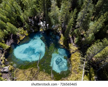 Blue geyser lake in forest from aerial view, Altai mountains, RUSSIA, ALTAI REPUBLIC
