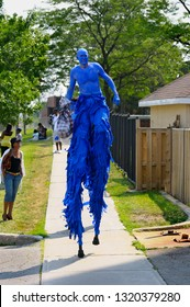 Blue giant walking on stilts on the sidewalk at the Junior Caribana Parade in Toronto, Ontario, Canada - July 19, 2008