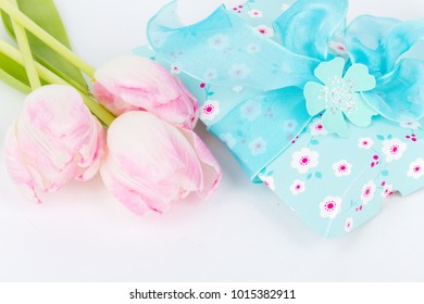 blue gift box decorated with blue bow and tulips