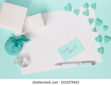 Blue gift box with jewelery and many small heart and flowers are all around. The background is blue. The best gift for any holiday. Mock up. Free space for text.