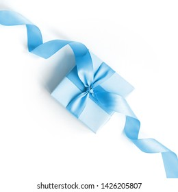 Blue gift box with a blue ribbon on a white background .  Holiday concept. Copy space. Flat lay.