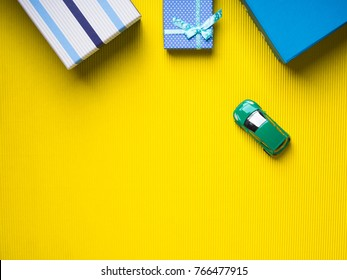 Blue Gift boxes and a toy car on vibrant yellow background. Christmas fathers day shopping. Travelling car insurance purchase concept