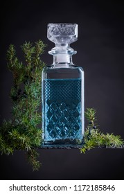 Blue gin in crystal decanter and juniper branch with berries on a black background.