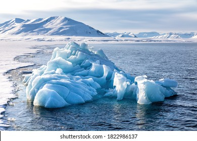 Blue glacial iceberg at the edge of the fast ice, Nordfjorden fjord. Svalbard,.