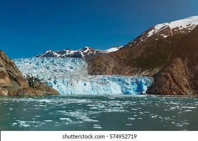 Blue glacier in mountain landscape. Travel destination in Alaska. Tracy Arm glacier tour
