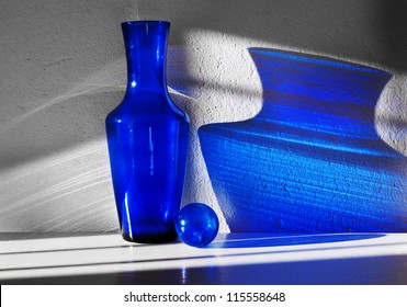 Blue Glass 2 - vase and globe lit by sunlight