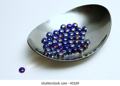 Blue glass beads in metal bowl