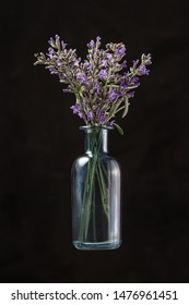 Blue glass bottle with lavender flowers on black background. Aromatherapy