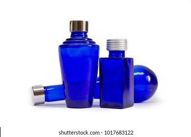 Blue glass bottles on white background. Three empty decorative cobalt blue bottles with silver lids, each a different design. Glassware intended for cosmetics, oils, perfumes, lotions and potions.