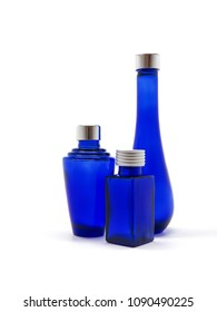 Blue glass bottles on white background. Three empty cobalt blue bottles with silver lids, each a different design. Glassware intended for cosmetics, oils, perfumes, lotions and potions. Vertical.