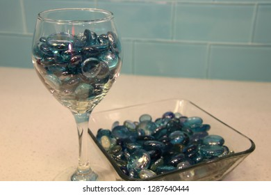 Blue glass circle pieces marbles in wine glass and bowl on granite quartz counter top with tile back splash.