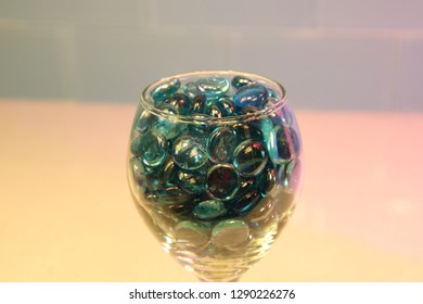 Blue glass circle pieces marbles in wine glass on granite quartz counter top with tile back splash.