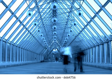 Blue glass corridor in bridge and people walking