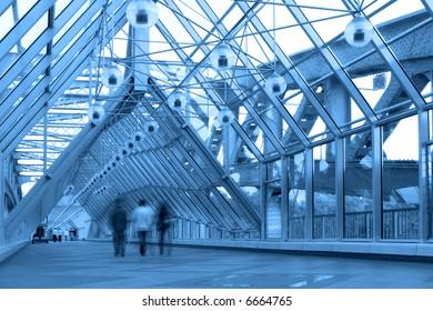 Blue glass corridor in bridge and people walking