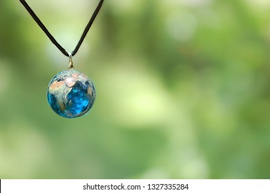 Blue Glass Earth Necklace on Green Background