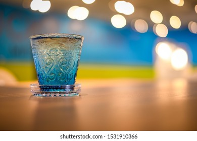 Blue glass on the wooden table behind the foreground
