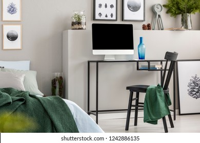 Blue glass vase next to all in one computer on industrial desk in forest inspired bedroom, real photo