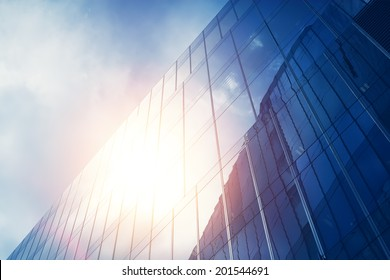 blue glass wall of skyscraper with sun reflection