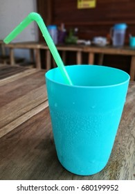 A blue glass of water with a green tube placed on a wooden table in a restaurant.