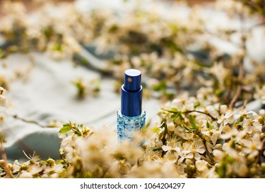 Blue Glass of water. Perfume bottle. Botle for woman. Cosmetics. White jasmine flower. branch of jasmine flowers. Tragic square funeral buttonhole from white jasmine flowers.