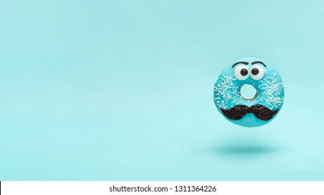 Blue glazed donut with mustache. Flying blue doughnut with funny face with mustache over blue background. Copy space for text. Masculinity or father day concept. Banner