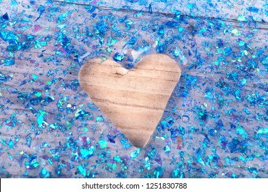 Blue glitter slime with a heart shape hole on a wooden table
