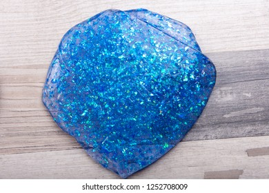 Blue glitter slime on a wooden table