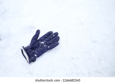 The blue glove fallen on the snow land in winter; the accessories for the skiers to keep warm